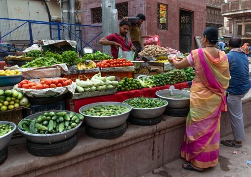 Indian man selling vegetables in a market, Rajasthan, Bikaner, India