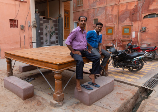 Indian men sit on a resting bed in front of a beautiful haveli in the old city, Rajasthan, Bikaner, India