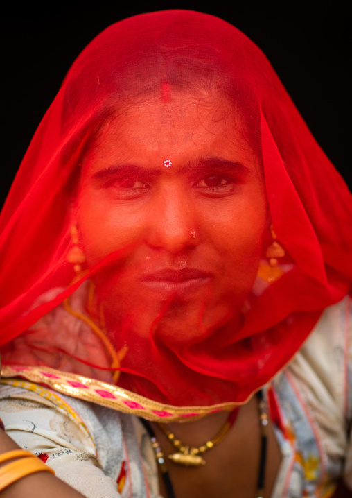 Portrait of a rajasthani woman hidding her face under a red sari, Rajasthan, Jaisalmer, India