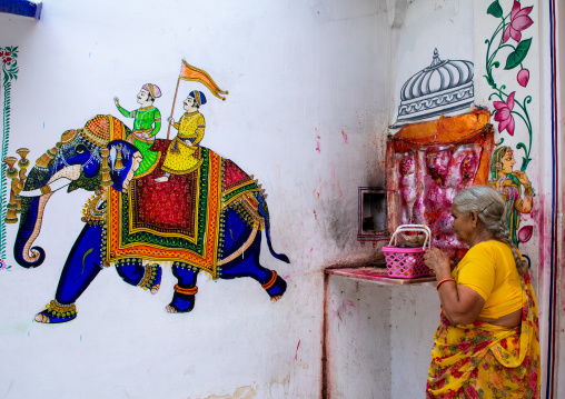 Indian woman praying in a temple decorated with murals depicting an elephant, Rajasthan, Udaipur, India