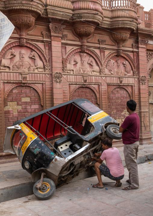 Indian men fixing a rickshaw in the street, Rajasthan, Bikaner, India