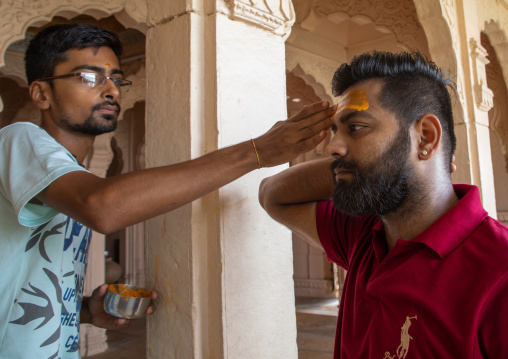 Indian man making a tika on the forehead of his friend in shiva temple, Rajasthan, Jaisalmer, India