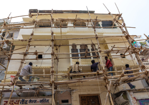 Indian workers on scaffoldings renovating the city palace, Rajasthan, Udaipur, India