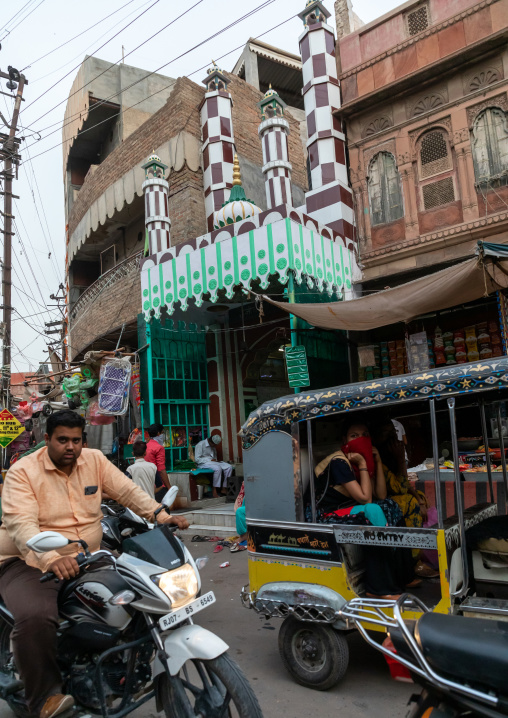 Indian riders ride motorbikes in front of a mosque, Rajasthan, Bikaner, India