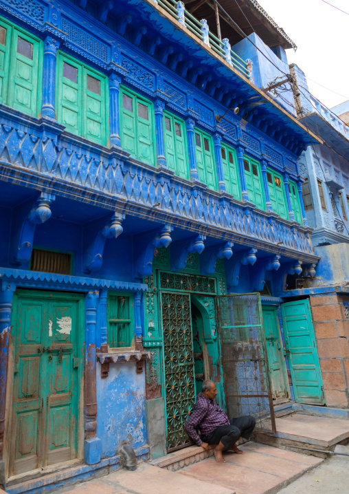 Indian man in front of an old blue house of a brahmin, Rajasthan, Jodhpur, India