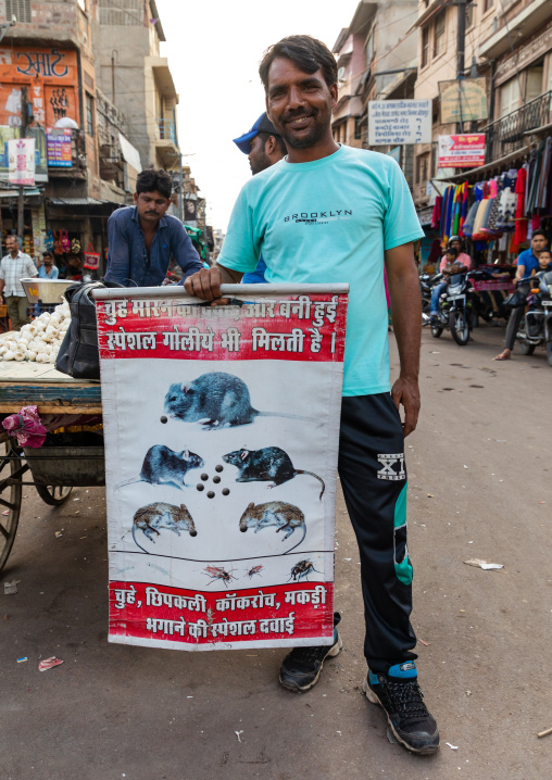Indian man in the street with a billboard for pest control, Rajasthan, Jodhpur, India