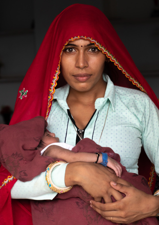 Portrait of a rajasthani woman with her baby in the arms, Rajasthan, Baswa, India
