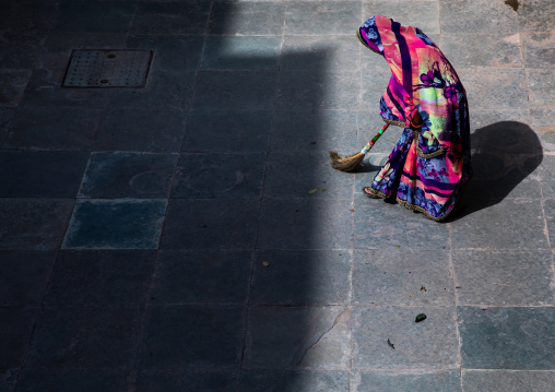 Indian woman cleaning a courtyard with a broom, Rajasthan, Bundi, India