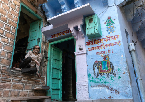 Indian man squatting near an old blue house of a brahmin, Rajasthan, Jodhpur, India