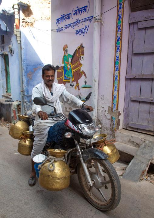 Indian man delivering fresh milk with his motorbike, Rajasthan, Bundi, India