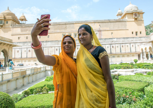 Indian women taking selfie in front of Amer fort and palace, Rajasthan, Amer, India