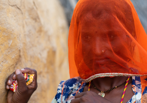 Portrait of a rajasthani woman hidding her face under an orange sari, Rajasthan, Jaisalmer, India
