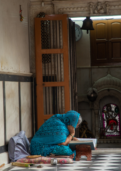 Indian woman reading a book in an old house, Rajasthan, Bikaner, India