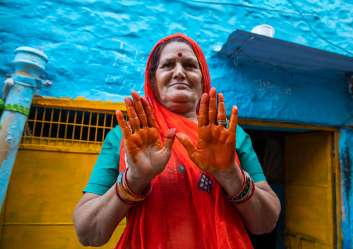 Portrait of a rajasthani woman in traditional sari showing her orange hands with henna, Rajasthan, Jodhpur, India