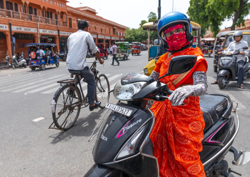 Indian woman in sari riding on scooter in the street, Rajasthan, Jaipur, India