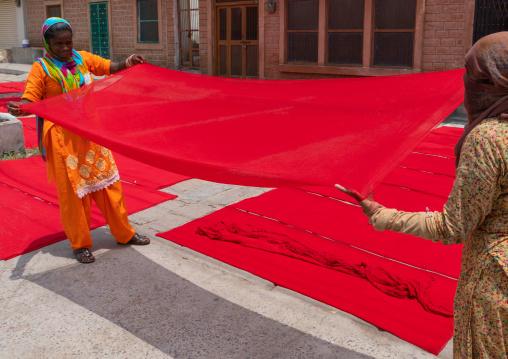 Indian women drying red saris in the street, Rajasthan, Jodhpur, India