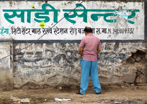 Indian man peeing outside on a wall, Rajasthan, Sawai Madhopur, India