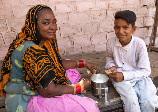 Portrait of rajasthani woman with her son having lunch in the street, Rajasthan, Jaisalmer, India