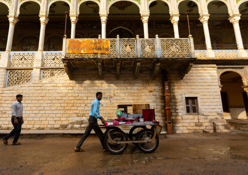 Indian man pushing a cart in front of an old historic haveli, Rajasthan, Nawalgarh, India