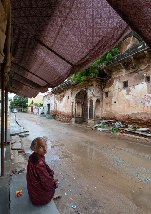 Indian man sit in front of an old historic haveli, Rajasthan, Nawalgarh, India