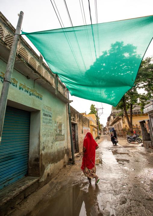 Indian woman walking in the street during the monsoon, Rajasthan, Nawalgarh, India