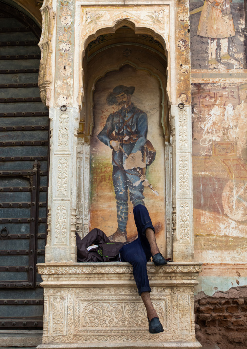 Indian man sleeping under a wall painting of an old haveli, Rajasthan, Nawalgarh, India