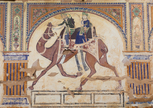 Wall paintings depicting indian people riding a camel on an old haveli, Rajasthan, Nawalgarh, India