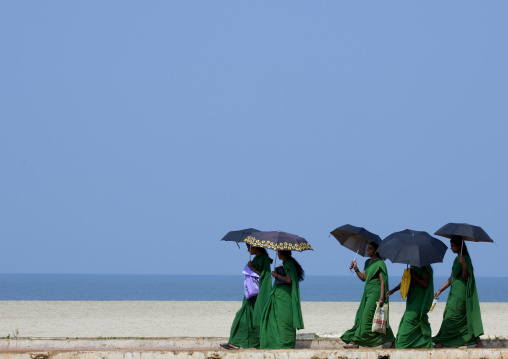 Group Of Young Women In Green Sari Holding Umbrellas Walking Down Alleppey Beach, India