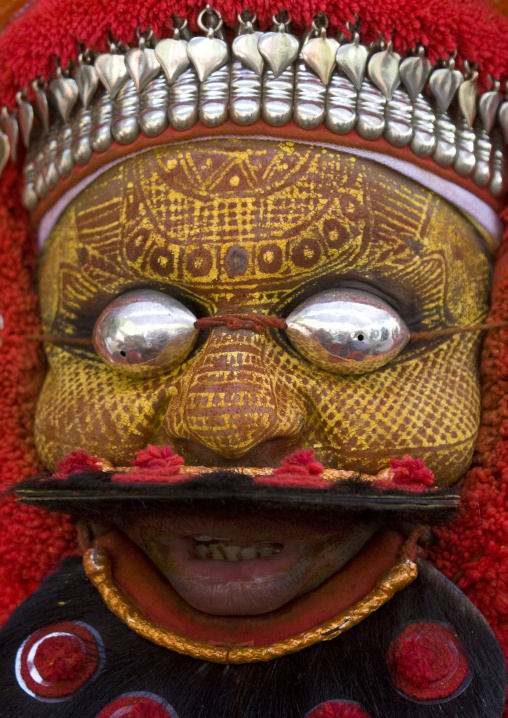 Man Dressed For Theyyam Ceremony With Traditional Painting On His Face And A Mask On His Eyes, Thalassery, India
