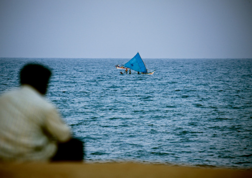 Man Sitting At Pondicherry Waterfront Looking At Fishermen On Their Boat, India