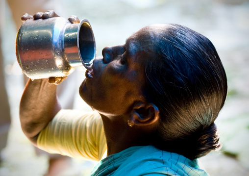 Woman Drinking Water Flowing From A Jug, Pondicherry, India