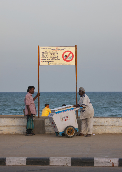 Ice-cream Seller Chatting With An Ohter Man In Front Of A No Swimming Sign At Pondicherry Seaside, India