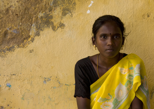 Indian Quiet Teenage Girl Sitting In Front Of A Yellow Decrepit Wall, Kumbakonam, India