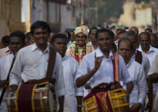 Young Groom Dressed For The Ceremony With Flower Garland Surrounded By Men  In White In Procession For The Wedding, Kanadukathan Chettinad, India