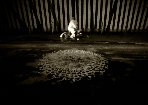Cyclist Riding Along A Kolam Drawned In The Street Near The Sri Ranganathaswamy Temple, Trichy, India