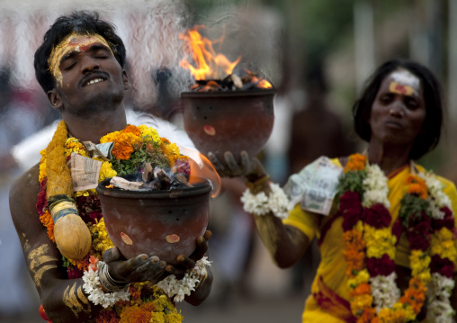 Indian Man And Woman With Traditional Painting On The Forehead In Procession Holding Jar On Fire As Offering During Fire Walking Ritual, Madurai, South India