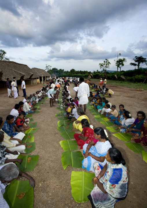 People Sitting On The Ground With A Leaf Serving As Plate During A Collective Meal After Fire Walking Ceremony, Madurai, India