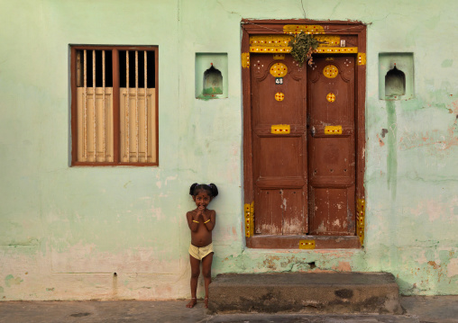 Little Girl With Hands Over The Mouth Posing In Front Of A House In Pondichery, India