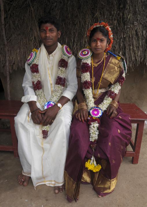 Young Bride And Groom Sitting On A Bank Dressed For The Ceremony And Adorned With Flower Garlands, Pondicherry, India