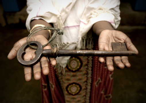 A Man Holds Out The Giant Key To A Mansion In Kanadukathan, Chettinad, India