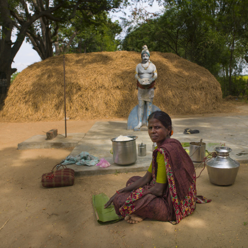 Woman Sitting On The Ground Preparing Food In Front Of A Hindu Statue And A Haystack, Pondicherry, India