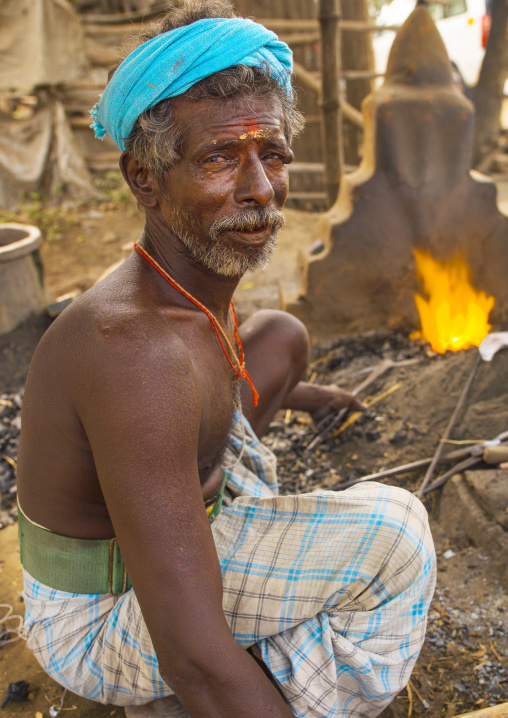 Blacksmith Holding His Tools Near A Flame In Pondicherry, India