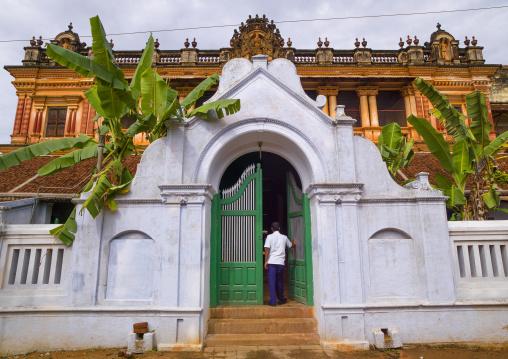 Man Opening The Portal Of A Old Chettiar Mansion With Banana Trees And Carvings Of Hindu Image, Kanadukathan Chettinad, India