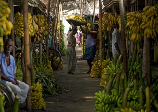Man Helping A Woman Holding A Basket At The Bananas' Section At Madurai Market, India