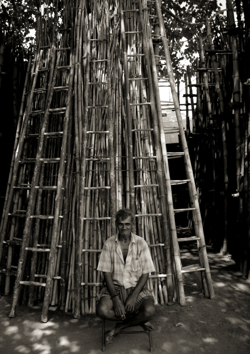 Old Amused Indian Man Sitting In The Shade Of Trees In Front Of Wooden Scales, Madurai, India