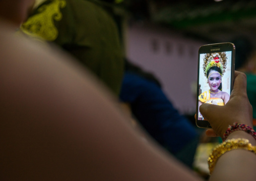 A Teenager Girl In Traditional  Costume Using Her Mobile Phone As A Mirror  Before A Tooth Filing Ceremony