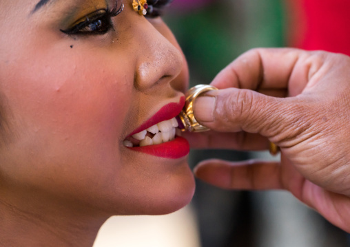 A Teenager Girl Having Her Teeth Blessed With A Ring By A Priest Before A Tooth Filing Ceremony