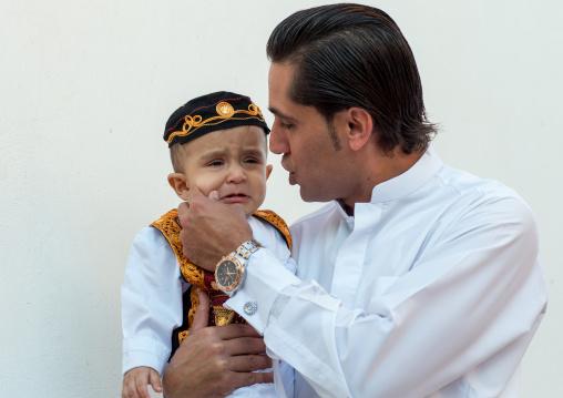 father with his crying son during a wedding ceremony, Hormozgan, Bandar-e Kong, Iran