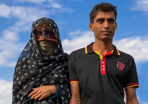 a bandari woman with her husband wearing a traditional mask called the burqa at panjshambe bazar, Hormozgan, Minab, Iran