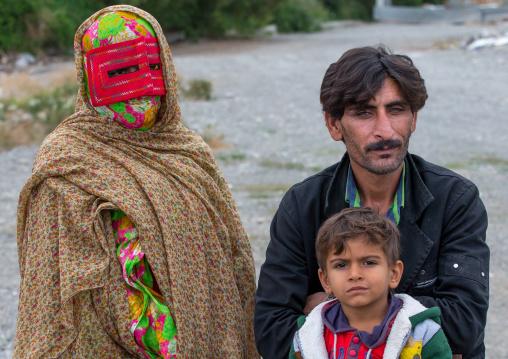 a bandari woman with her husband and son wearing a traditional mask called the burqa at panjshambe bazar thursday market, Hormozgan, Minab, Iran